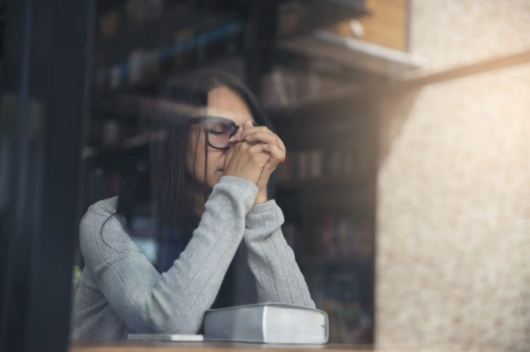 Beautiful woman wearing gray sweater and glasses sitting in a library ,she is sad and stressful with her job on the table.
