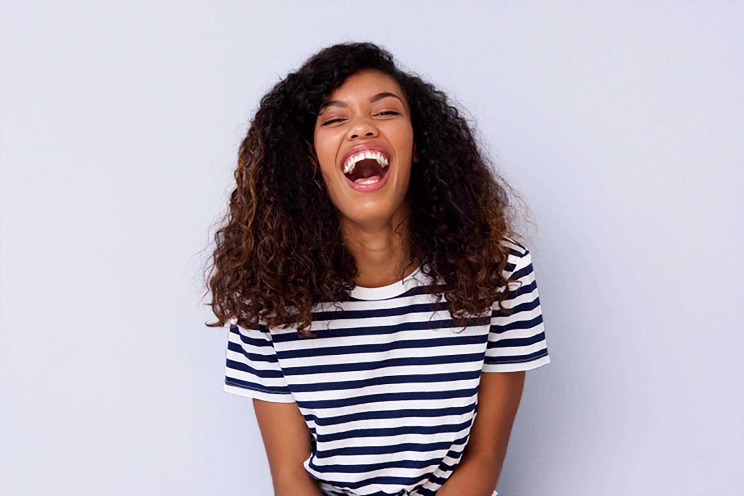 Portrait of young black woman laughing against gray wall