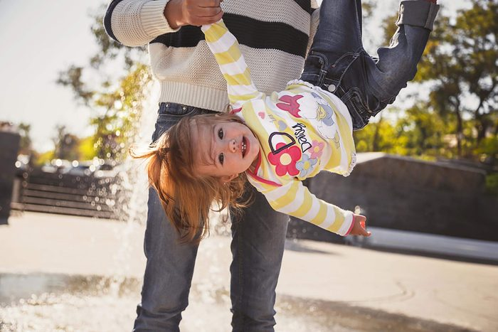 ODESSA, UKRAINE - OCTOBER 5, 2014: Close up of happy cheerful family, mother and little daughter in Disney Daisy Duck pullover playing in park next to fountain, mom is holding small girl upside down