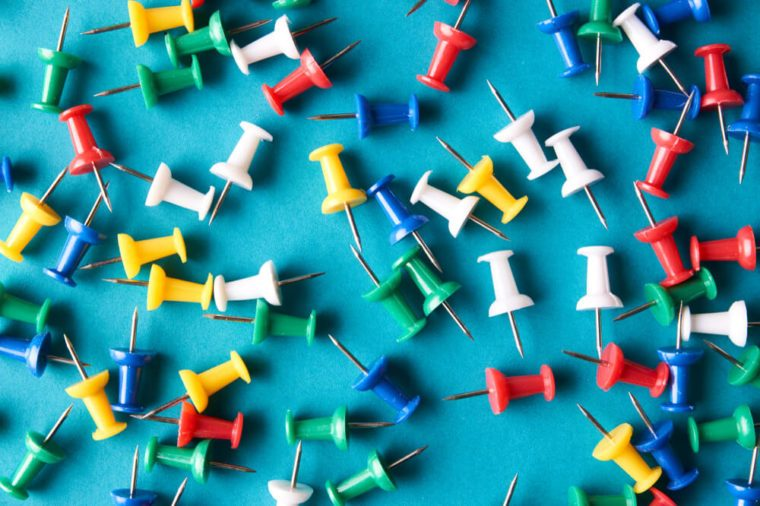 Push pins on blue background, close-up. Colorful Pushpins or colored thumbtacks to remember things to do concept.
