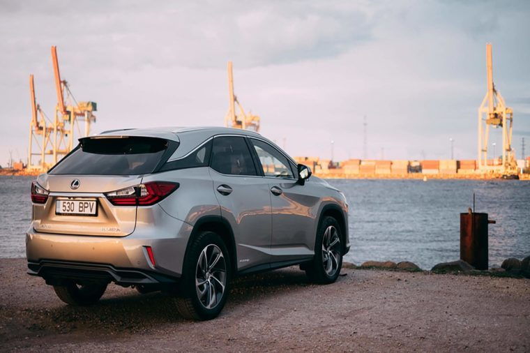 RIGA, APRIL 2016 - A Lexus RX450h hybrid luxury SUV is parked near river with a view of freight port in the background
