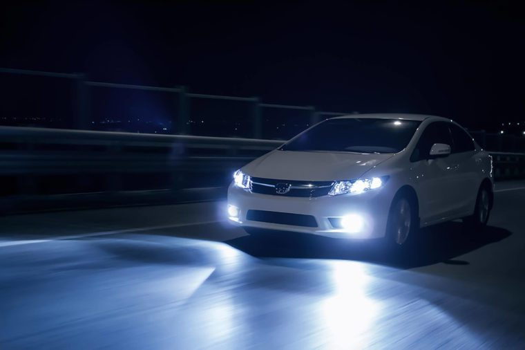 Saratov, Russia - October 23, 2012: White car Honda Civic with xenon headlights fast drive on road at night