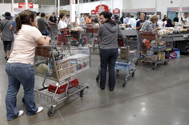 Shoppers wait at the check-out line at Costco Wholesale in Mountain View, Calif. Costco Wholesale Corp.'s fiscal fourth-quarter net income climbed 11 percent as the wholesale club operator made more money on membership fees and saw its sales rise