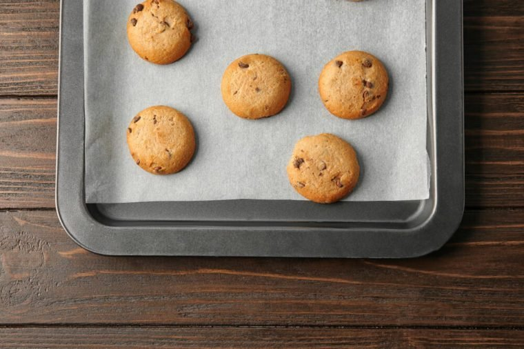Delicious oatmeal cookies with chocolate chips on baking sheet