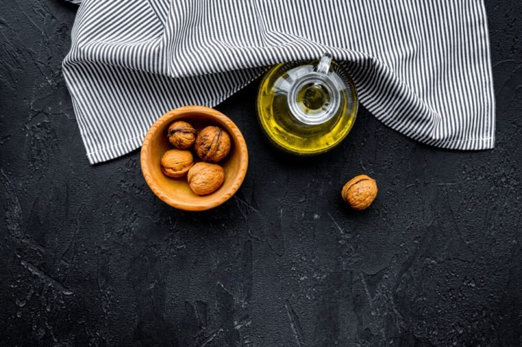 Nut oil for skin care or cooking. Walnut oil in jar near walnut in bowl on black background top view copy space