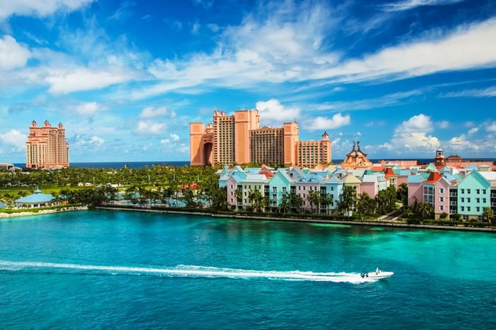 Beautiful scene of speed boat, ocean, colorful houses and a hotel in Nassau, Bahamas on a summer sunny day