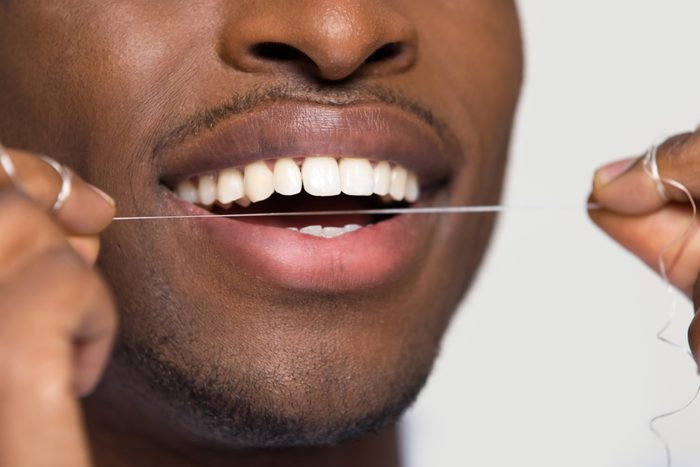 Close up view of african american black man cleaning white healthy teeth holding using dental floss isolated on grey studio blank background, oral hygiene concept, tooth health care caries prevention