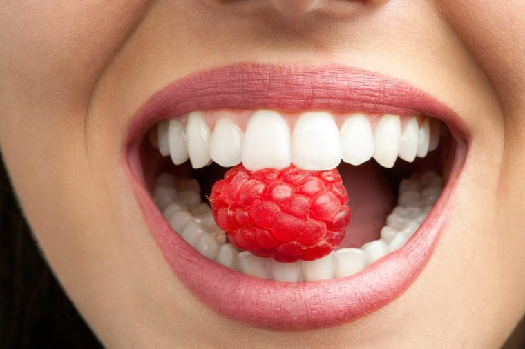Macro close up of healthy female teeth biting raspberry.