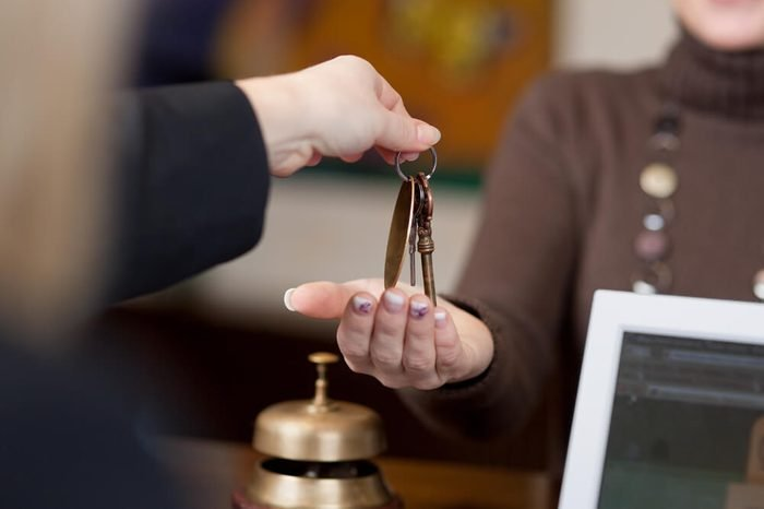 Receptionist giving room keys to customer at reception in hotel