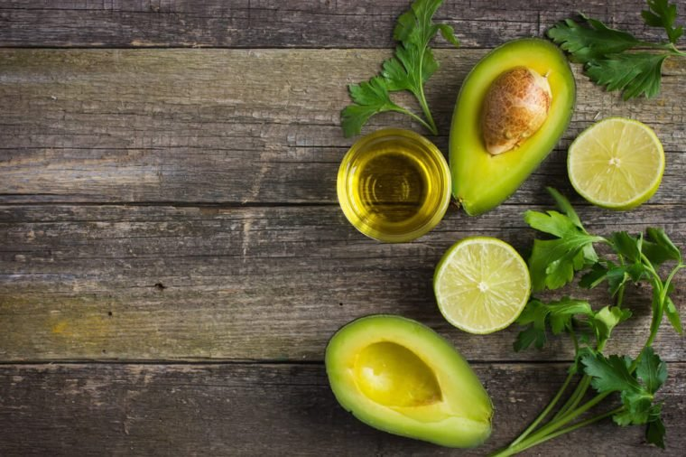 food background with fresh organic avocado, lime, parsley and olive oil on old wooden table, top view, copy space