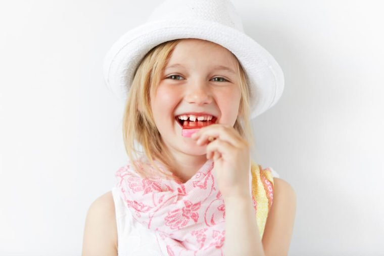 Small European girl laughing at camera and eating lollipop in white morning light. Holiday mood and cheerful atmosphere mixed with shinny white look of kid and her happy-go-lucky style.