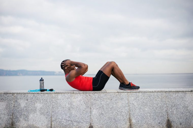 Man doing sit ups. Core outdoor workout. Black athlete exercising.