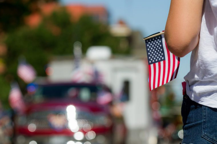 Girl holding an american flag with a parade float in the background