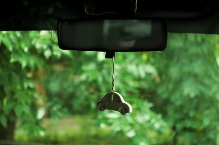Air freshener hanging in the car on green natural background