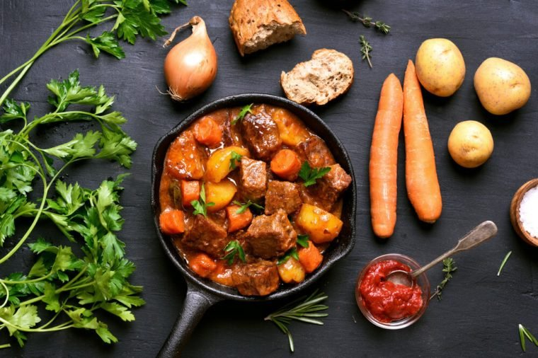Stewed beef with potatoes and carrots in cast iron pan on dark background, top view