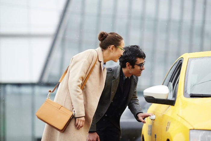 Two business people, man and woman, catching yellow taxi in street of rainy autumn city