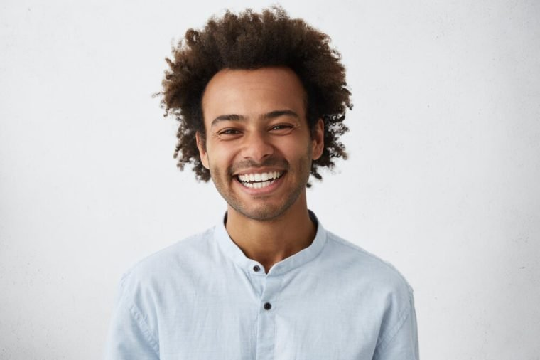 Friendly looking positive Afro American stylish man with funky hair and bristle smiling broadly during nice conversation with good old friend, standing isolated at grey studio wall. Horizontal
