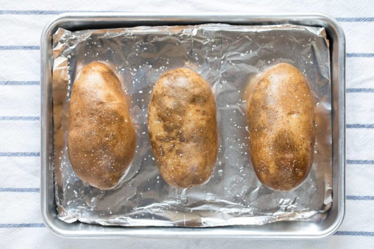 Vertical overhead perspective of three oiled brown uncooked baked russet potatoes sprinkled with kosher salt flakes arranged in row on aluminum foil lined metal quarter sheet pan for oven baking
