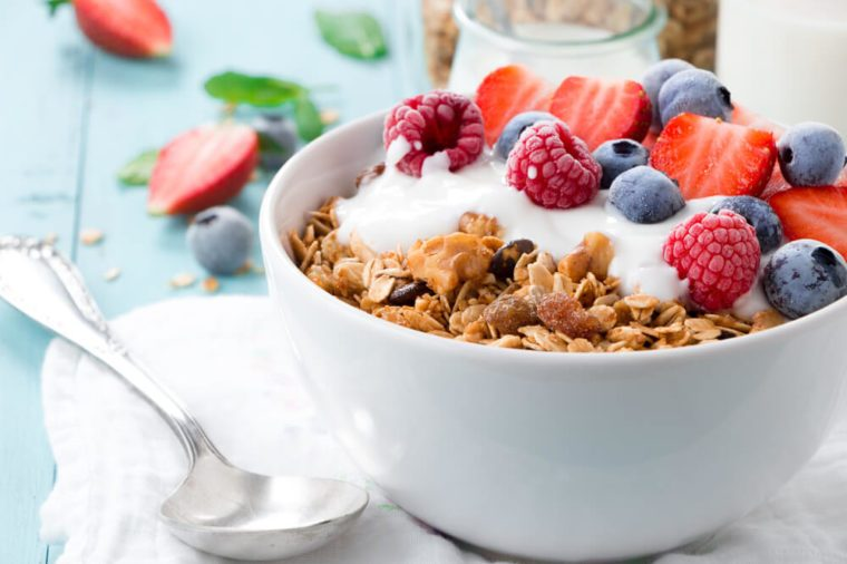Healthy breakfast in a bowl with homemade baked granola, frozen berries, fresh strawberries and yogurt on a turquoise wooden table
