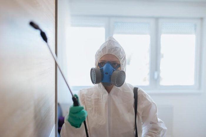 Exterminator in workwear spraying pesticide with sprayer.