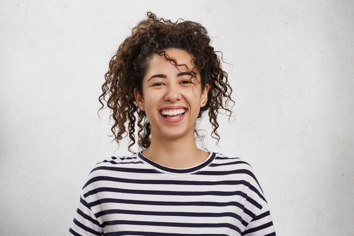 Positive emotions concept. Emotional happy young woman with crisp hair, appealing appearance and broad charming smile, rejoices her success or being glad to organize unforgettable party with friends
