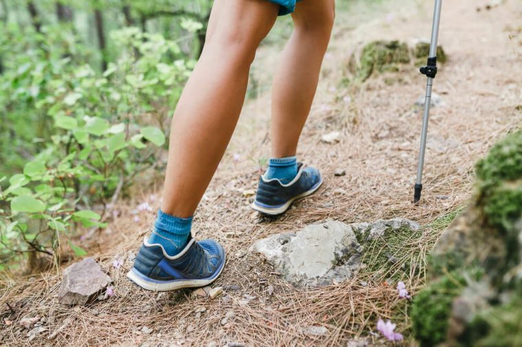 Closeup of young fitness woman legs walking on forest hiking trail