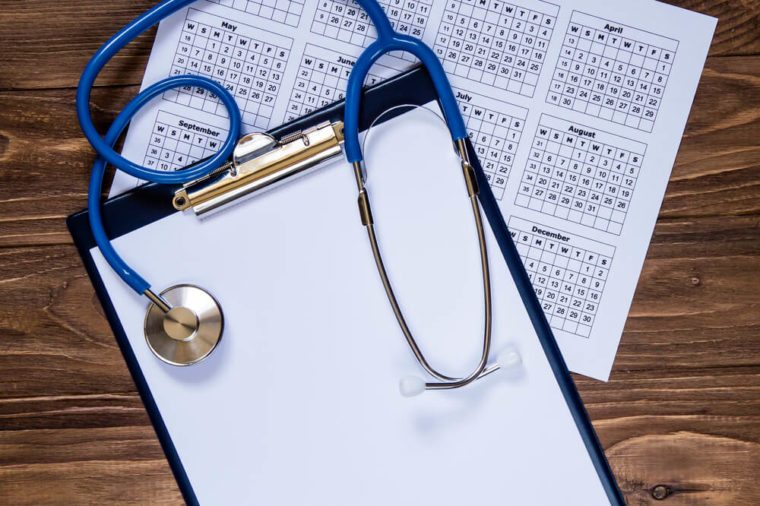 Exam pad, calendar and stethoscope on the smooth wooden table