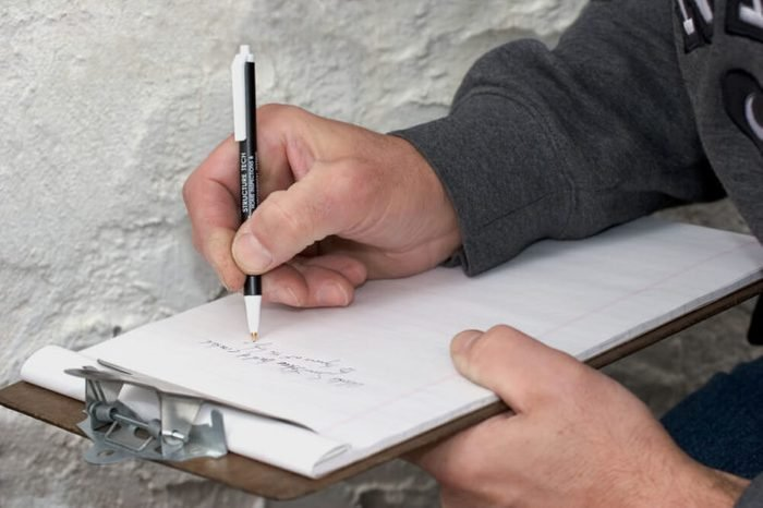 A housing inspector making notes during an inspection