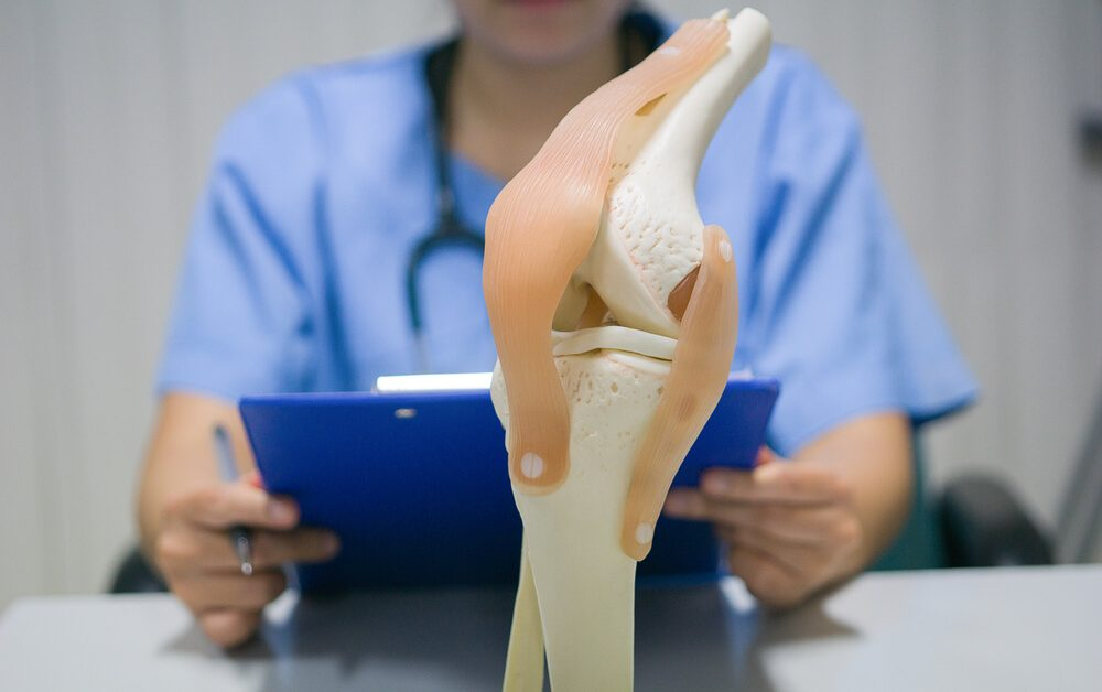An orthopedic surgeon reads a patient's knee replacement report for analysis and guidelines for postoperative treatment and allows the patient to live a normal life. medical and orthopedic concept.