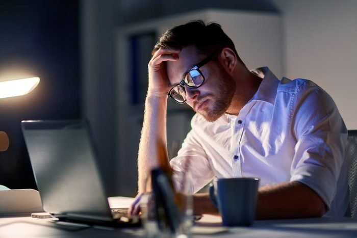 business, overwork, people, deadline and technology concept - stressed businessman in glasses with laptop computer thinking at night office