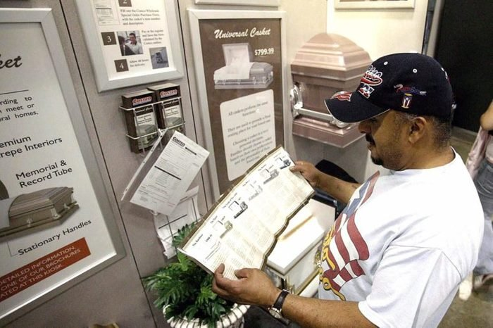 Tomas Torres Reads a Brochure Which Shows the Prices and the Size Options of Coffins in Front of the Casket Display Inside a Costco Warehouse Store in Chicago August 24 2004 the World's Largest Warehouse Club Operator Said on Tuesday It Began a Test Program That Offers Coffins at Two of Its Chicago Area Stores the Issaquah Washington-based Company Said the Two Stores Are Now Offering Six Different Models of Steel Coffins That Are Made by Universal Casket Co Based in Michigan the Retailer Has Set Up a Special Order Program in Which Customers Can Select a Coffins in Either of the Two Locations and Have It Shipped to Their Mortuary of C United States Chicago