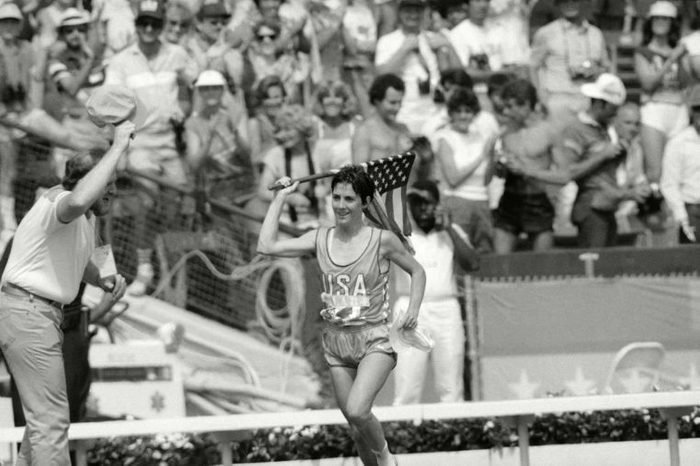 Twenty-seven-years-old Joan Benoit of Freeport, Maine, waves the American flag enthusiastically in Los Angeles after finishing the first-ever Olympic women's marathon in the fastest-ever time for that distance. 2.24:52 for the 26-mile, 385-yard course