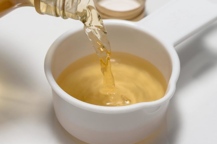 Pouring a quarter cup of apple cider vinegar