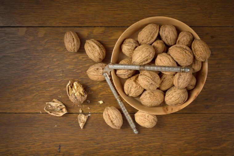 Above View of Walnuts grown in Oregon, in a Wooden Bowl on a Dark wood Table Background with some cracked and the nutcracker. It's horizontal with room or space for copy, text, crop or your words