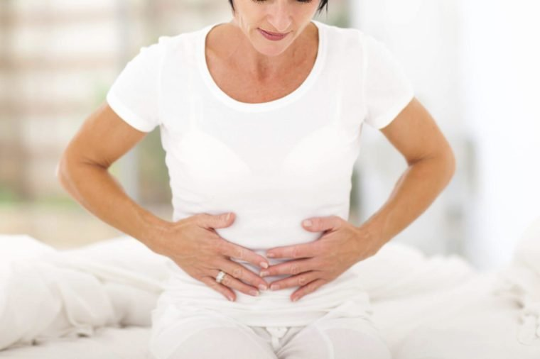 meados idade mulher tendo dor de estômago