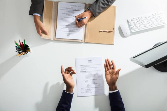 Elevated View Of Businessperson And Candidates Hand With Resume On White Desk