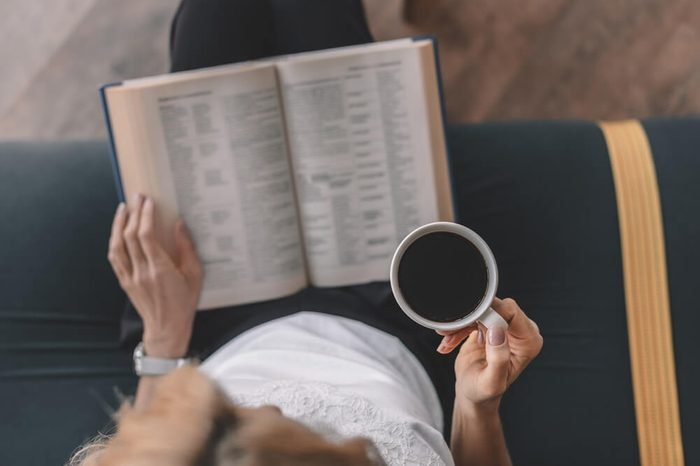 overhead view of woman reading book and drinking coffee in cafe