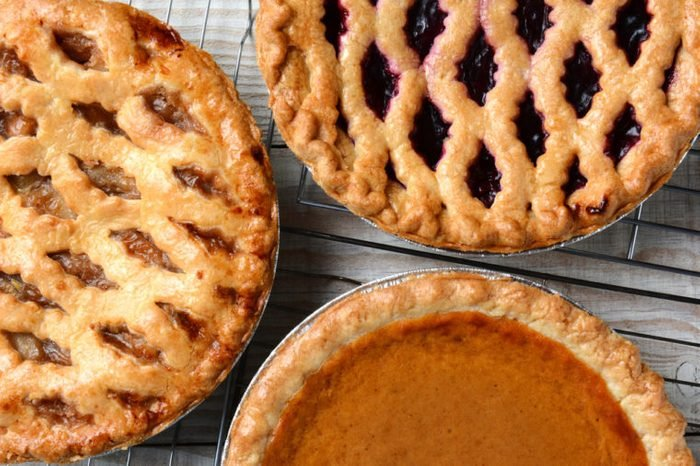 Three pies on cooling racks. High angle closeup shot of fresh baked apple, cherry and pumpkin pastries on wire racks on a rustic wood kitchen table. Horizontal format.