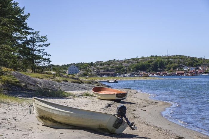 Boats on the shore of South Koster island and view of Nordkoster on North Koster island, Bohuslan County, Sweden.
