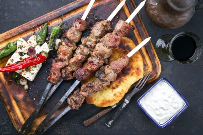 Traditional Greek Souvlaki with Feta and Pita Bread as top view on an old burnt cutting board