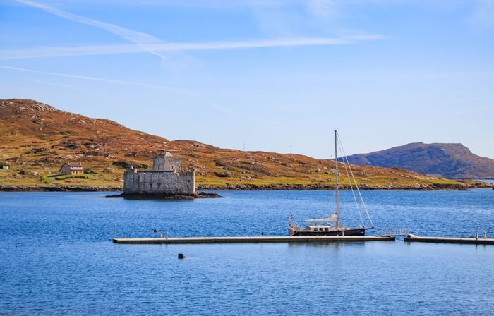 Kisimul Castle on the island of Barra, one of the outer hebrides islands and a sailing boat moored on the new marina poonton