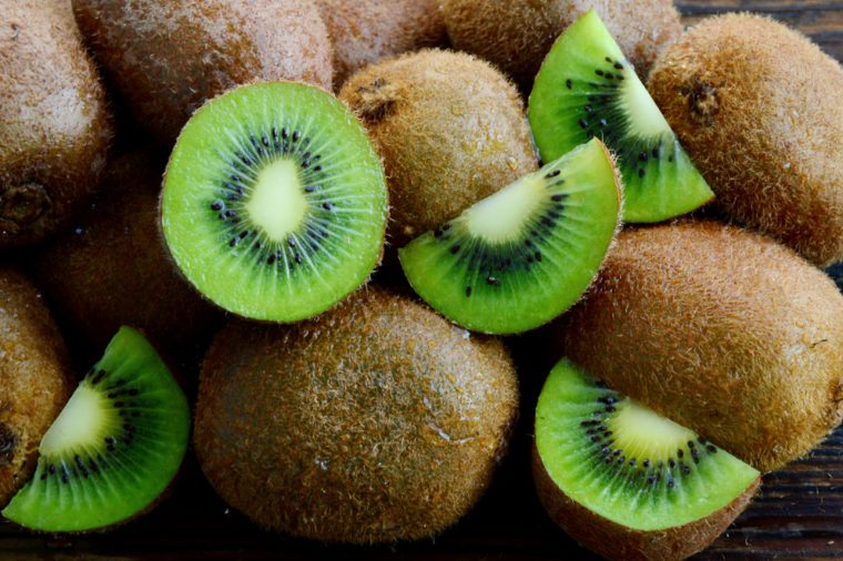 A lot of fresh Kiwi fruits on wooden floor.Kiwis are a nutrient dense food, they are high in nutrients and low in calories.