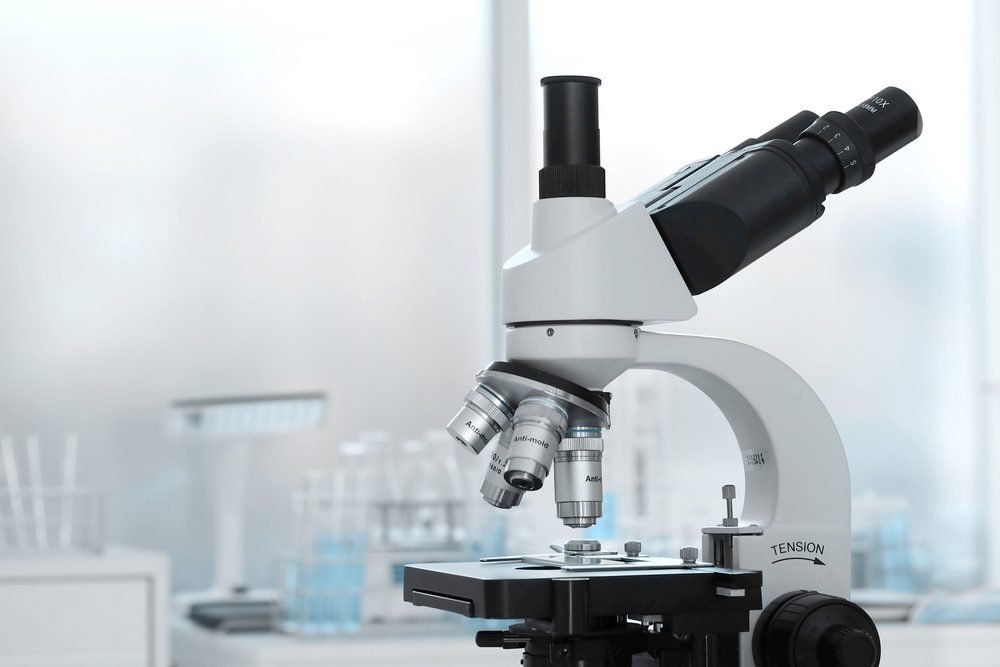 Laboratory lens of Microscope Isolated blue scientific research background