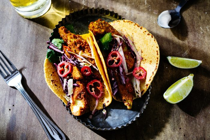 Overhead of fried avocado tacos with red cabbage slaw and sliced red jalapenos in metal tray with lime wedges and beer on wooden surface.