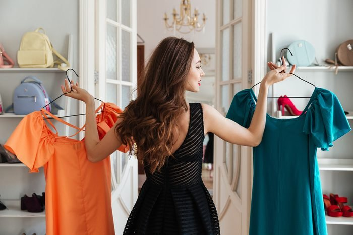 Image of young lady standing in clothes shop indoors choosing dresses. Looking aside.