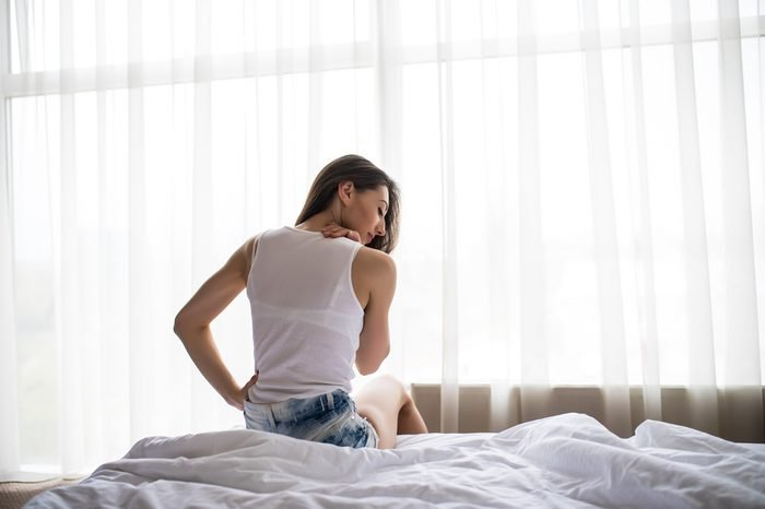 Young Woman Sitting On Bed Having Back Pain