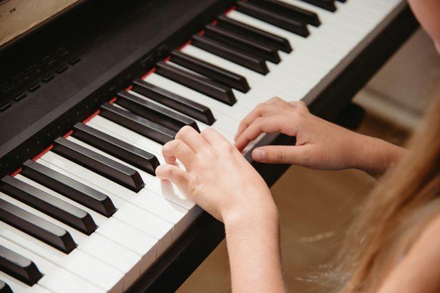 Close up hands playing keyboard.