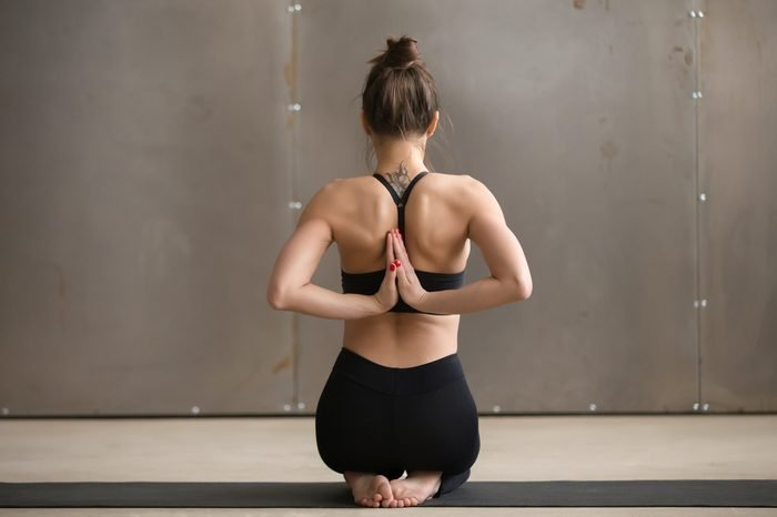 Young yogi woman practicing yoga, sitting in Vajrasana pose with Namaste behind the back, working out wearing black sportswear, cool urban style grey studio background, full length, rear view