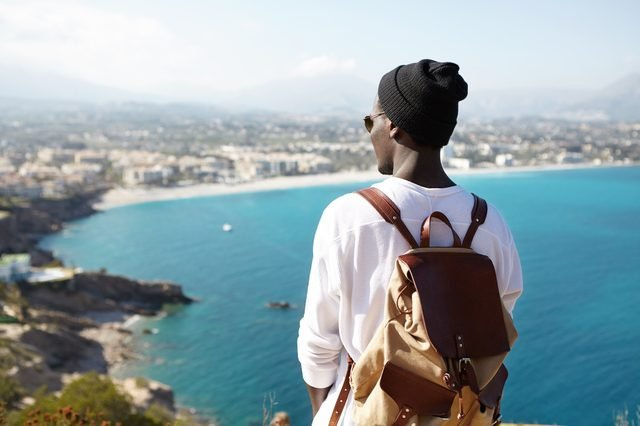 Rear view portrait of young African American backpacker facing sea standing on viewing platform or rock, admiring fascinating views in European resort city, dressed casually. People and travelling