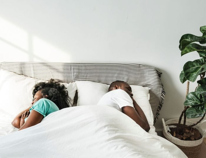 Black couple sleeping together on bed back to back